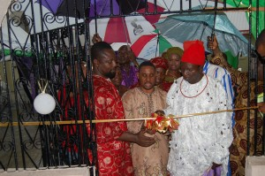 Rev. (Dr.) J.A. Ottuh cutting the tape to commission the hotel and assisted by Mr. Fred Atsiangbe (Left) and Chief Patrick Ogiba (Right)